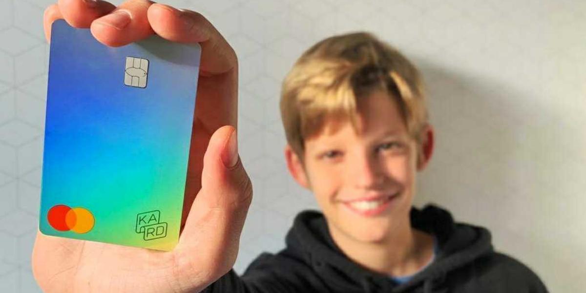 Un ado de 10 ans montre une carte de paiement Kard pour apprendre à gérer son argent de poche