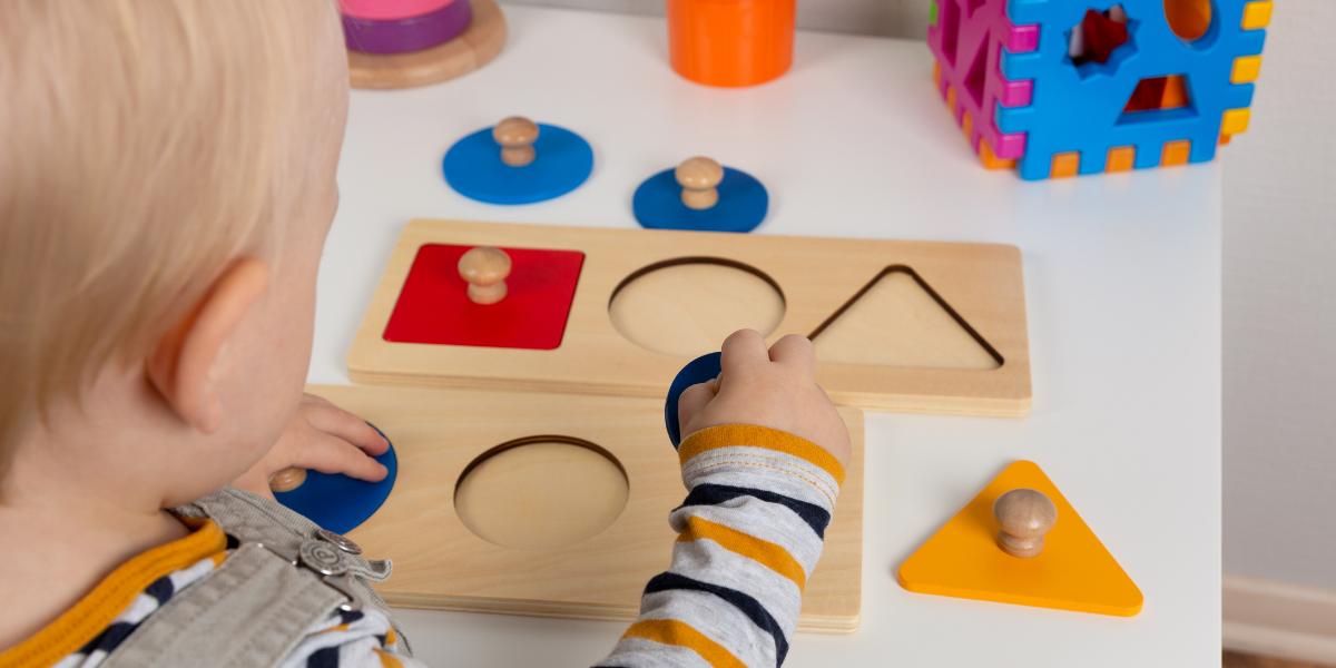 main d'enfant en train de jouer avec un jeu d'encastrement