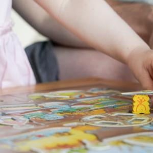 un plateau de jeu de société avec une main d'enfant et une main d'adulte